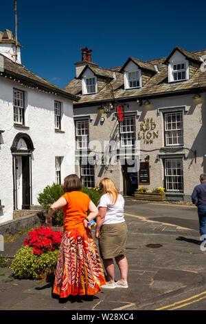 UK, Cumbria, Hawkshead, Wordsworth Street, women admiring floral planter opposite Red Lion Pub - Stock Image