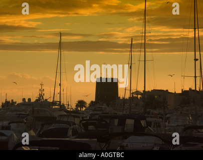 Puerto Banus sunset Costa del Sol Spain sunset sunsets watchtower watchtowers tower towers playground of the rich mast masts - Stock Image