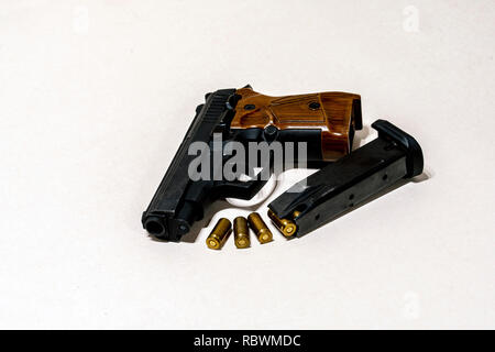 the pistol with cartridges on a light background - Stock Image