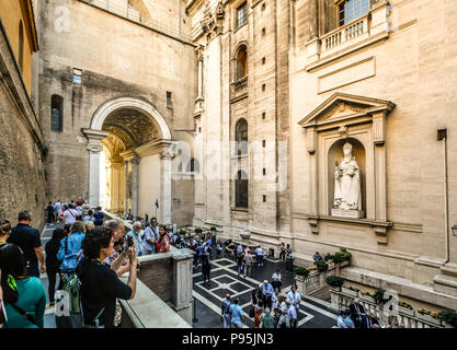 Tourists drink from the water fountain just inside the massive gated entrance to the Vatican Museum in Vatican City - Stock Image