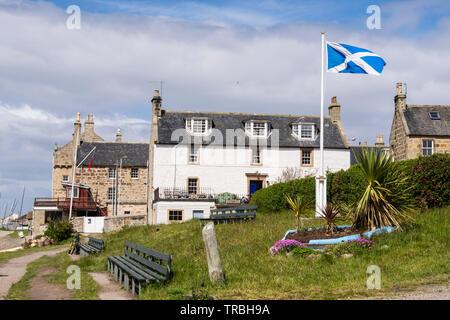 Scottish flag flying outside old buildings in coastal village of Findhorn, Moray, Scotland, UK, Britain - Stock Image