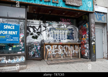 A vacant store for rent on Houston Street in Manhattan covered in graffiti, stickers and tags. Lower East Side, New York City. - Stock Image