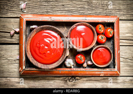 Tomato sauce with spices. On a wooden background. - Stock Image