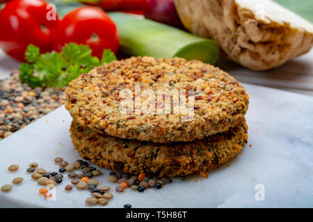 Tasty vegetarian food, raw burgers made from lentils legumes with vegetables ready for cooking, good for vegans - Stock Image