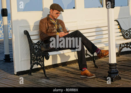 checking phone messages at brightion Palace Puierm Brighton, United kingdom - Stock Image