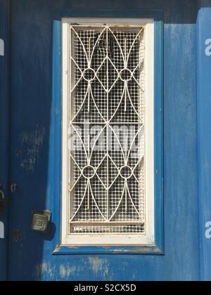 Window with decorative ironwork cover, Greek islands - Stock Image