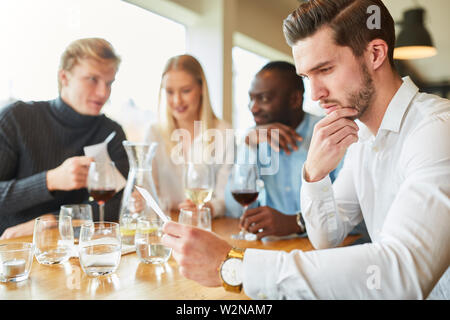 Young man as a guest with a menu in the restaurant considers his order - Stock Image