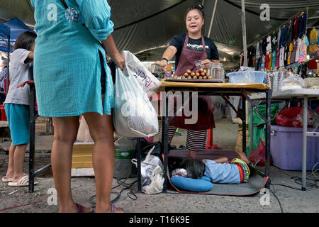 Working mother. Child asleep under her mothers food stall. Thailand, Southeast Asia - Stock Image