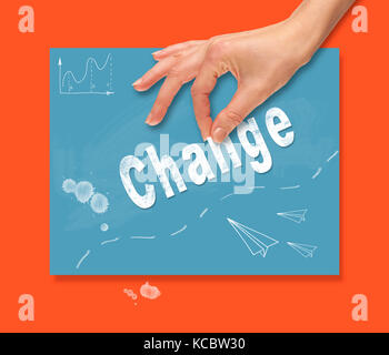 A hand picking up a Change concept on a colorful drawing board. - Stock Image