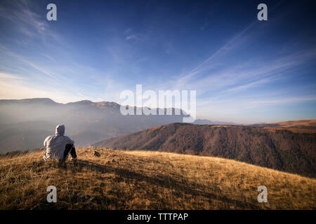 Rear view of man looking at view while sitting on Carpathian mountains - Stock Image
