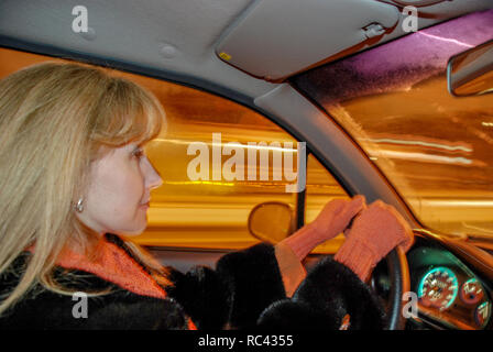 girl in a fur coat and pink gloves driving. Outside the window traces of headlights from passing cars - Stock Image