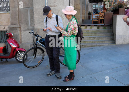 An older Japanese couple navigating the streets of Porto with maps on their mobile phones in a street in Portugal Europe   KATHY DEWITT - Stock Image