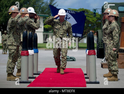 170701-N-YG415-406 OKINAWA, Japan (July 01, 2017) Cmdr. Joseph D. Harder renders a salute while being piped aboard during a change of command ceremony for Naval Mobile Construction Battalion (NMCB) 3. Harder assumed command of NMCB 3 from Cmdr. Laurie Scott during a change of command ceremony at Camp Shields Okinawa, Japan. (U.S. Navy photo by Mass Communication Specialist 1st Class Michael Gomez/Released) - Stock Image