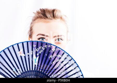 Shy girl, girl with fan, girl using fan, chinese fan, rigid fan, fixed fan, hiding behind fan, sharp eyes, eyes, pretty eyes, stunning, fresh skin, - Stock Image