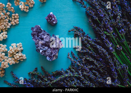 Amethyst Crystal with Lavender and Flowers on Turquoise Table - Stock Image
