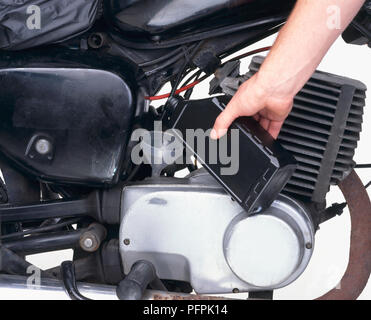 Replacing the gearbox oil using a funnel to prevent spillage. - Stock Image