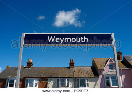 Weymouth - place name sign at the railway station, along with nearby properties, in Dorset, UK. - Stock Image