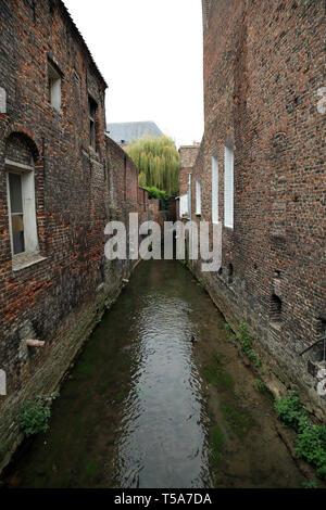 View of river flowing between buildings from Place du Castel, Aire sur la Lys, Pas de Calais, Hauts de France, France - Stock Image