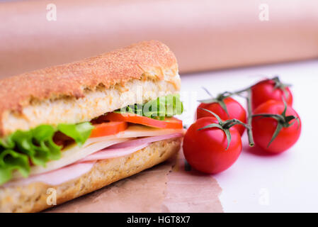 Fresh crusty baguette with ham, cheese, tomato and green salad - Stock Image
