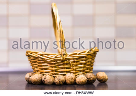 Whole walnuts in front of a wicker basket on a - Stock Image