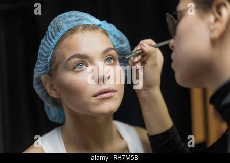 Makeup artist applying makeup to eyes of young woman wearing shower cap - Stock Image