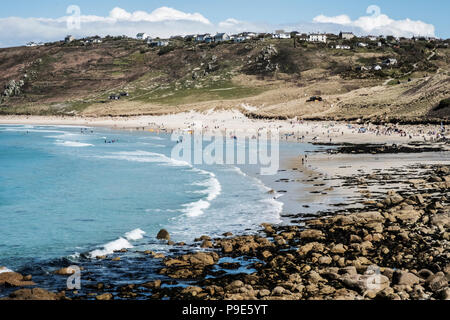 View along a coastline and sandy beach, waves breaking and people on the shore, with houses on the overlooking cliffs. - Stock Image