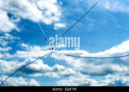 Single accurate cracked glass window with a blue sky background and white summer clouds - Stock Image