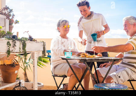 grandfathers adult mature and teenager nephew enjoy outdoor in the terrace some leisure with food and drinks. ocean and city view, vacation sunny day  - Stock Image