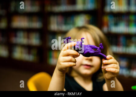 A 4-year old girl holds a dinosaur up for the camera while playing with toys at a library. - Stock Image