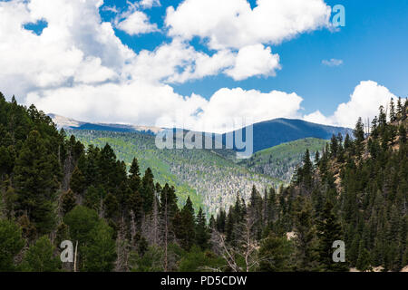 Rolling, overlapping  green mountains, V-shaped view, with white, puffy clouds and blue sky.   Good for background. - Stock Image