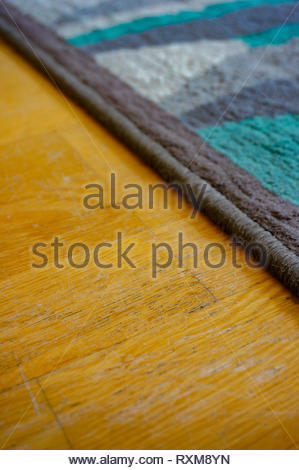 Close up of a blue and gray carpet edge on a wooden floor. - Stock Image