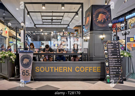 Customers browsing their cell phones at a coffee bar. Thailand, Southeast Asia - Stock Image