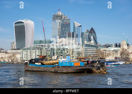 Barge on the river Thames London full of scrap metal with a view of the city of London in the background - Stock Image