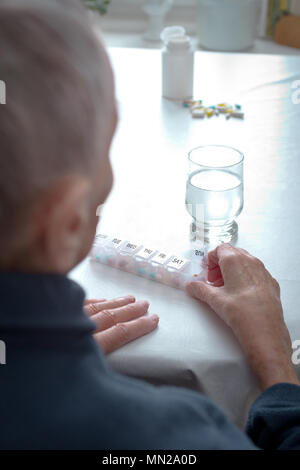 Old woman sitting at a table at home with a glass of water and lots of capsules in different colors in a presorted weekly pill dispenser. - Stock Image