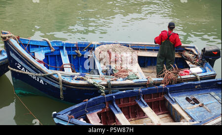 A fisherman preparing to go fishing in a traditional blue boat in Essaouira - Stock Image