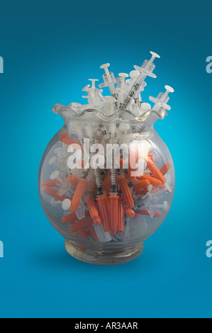 About fifty used syringes packed into a jar - Stock Image