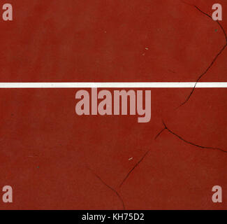 Pole aerial image of an outdoor basketball court. Includes pavement cracks, white line and red surface. - Stock Image