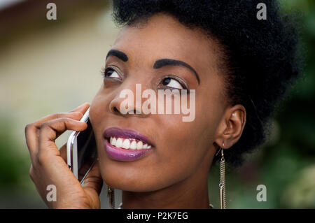 Close-up portrait of beautiful young woman smiling in communication - Stock Image