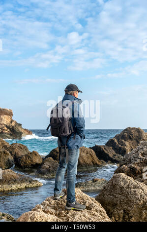 man wearing a backpack standing on a rock looking out to sea - Stock Image