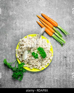 Porridge with herbs. On rustic background - Stock Image