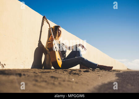 Beautiful girl sitted on the street with her guitar. Freedom concept. Blue sky on background - Stock Image