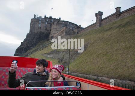 A young couple on an open-top bus tour of Edinburgh Scotland - Stock Image