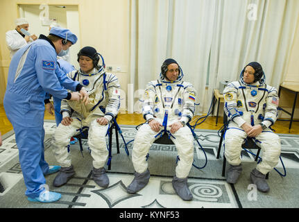 Expedition 54 flight engineer Norishige Kanai of the Japan Aerospace Exploration Agency (JAXA), left, is helped - Stock Image