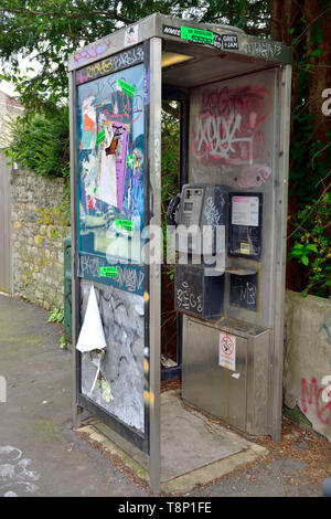 Modern British phone box vandalized with posters, tagging and graffiti - Stock Image