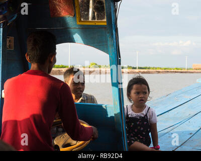 Helmsman's daughter and son with him on trip while driving tourist boat to see Kompong Stilted village on Tonle Sap Lake Siem Reap Cambodia Asia - Stock Image
