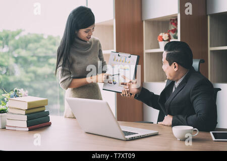 Happy asian businesswoman presenting pile chart to manager in office. Business presentation and meeting concept. - Stock Image