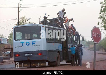 Yako town, Burkina Faso: loading a motobike onto a bus roof for a long journey. - Stock Image
