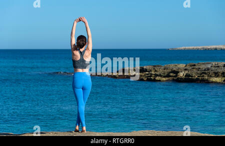 back view of a woman doing an arm stretch above her head by the mediterranean sea - Stock Image