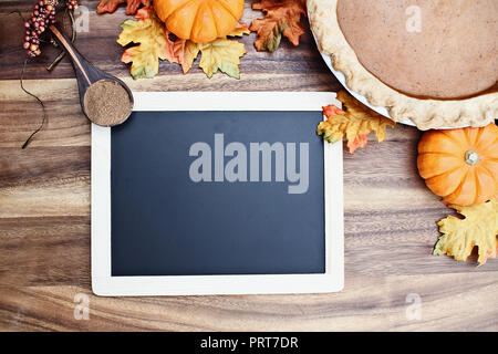 Homemade pumpkin pie in pie plate with little pumpkins, leaves, spice and blackboard with room for recipe or text over rustic wooden background. - Stock Image
