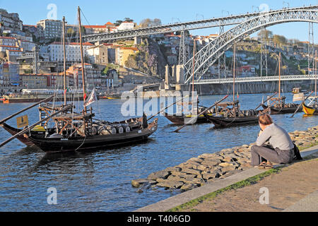 A young woman sitting on the waterfront with a view of Dom Luis I Bridge, River Douro winery boats and Ribeira in Porto Portugal Europe  KATHY DEWITT - Stock Image